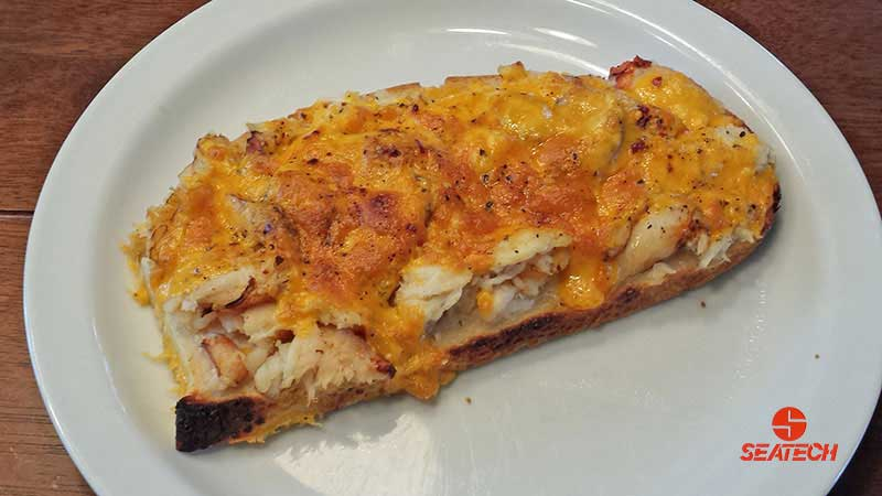 A photograph of a Chilean crab meat melted cheese open face sandwich.