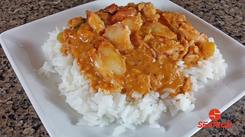 A photograph of Chilean crab meat and red Indian curry sauce over rice.