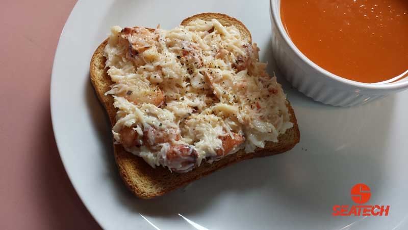 A photograph of crab salad meat on toast with a cup of tomato soup placed next to it.