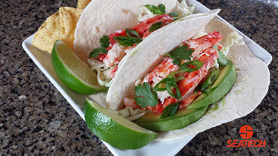A photograph of Chilean king crab tacos with king crab meta, avocados, cilantro, shredded cabbage and a sour cream dressing