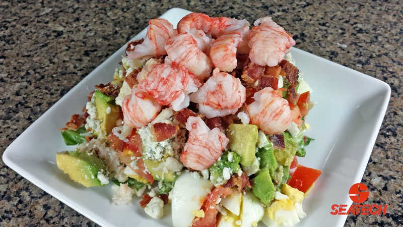A photograph of langostino lobster COBB salad with langositino, boiled eggs, bacon, avocado, blue cheese, tomatos and lettuce