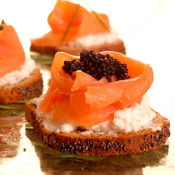 A photograph of cold smoked salmon on crostinni with salmon mouse and caviar