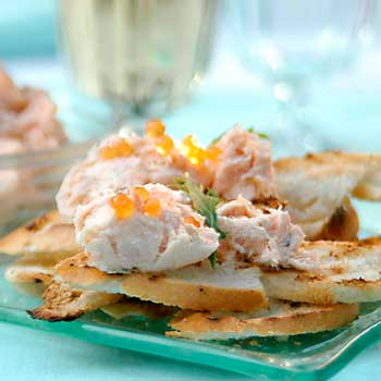 A photograph of cooked salmon spread on toast with salmon roe.