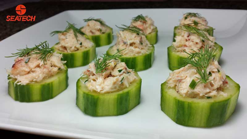 A portograph of English cucumber slices topped wtih crab salad and fresh dill.