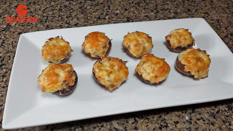 Mushrooms stuffed with crab meat, cheese and chives topped with more cheese and backed.