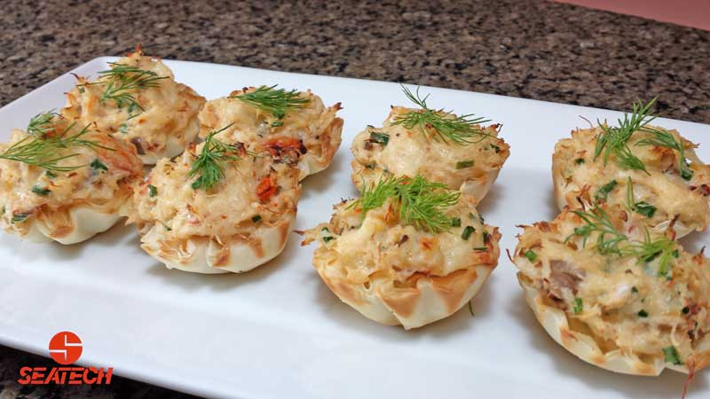 Phyllo cups stuffed with crab meat, cheese, cream cheese and chives with a fresh dill garnish.