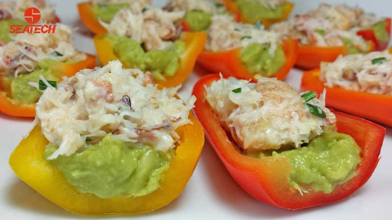 A photograph of mini sweet bell peppers stuffed with crab salad and guacamole