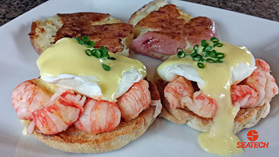 A photograph of langostino eggs benedict with smashed potatoes.