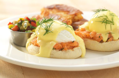 A photograph of salmon tartar eggs benedict wtih an avocado salsa and smashed red potatoes.