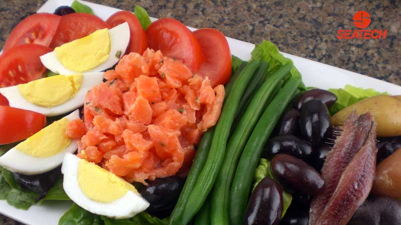 A photograph of salmon tartar nicoise salad with hard boild eggs, green beans, olives, potatoes, anchovies, tomatoes and salmon tartar.