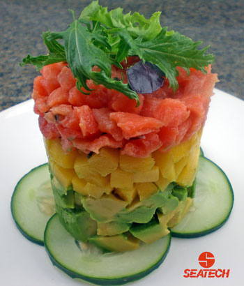 A photograph of a salmon tartar tower with salmon tartar on diced mangos on doced avocado topped with micro greens.
