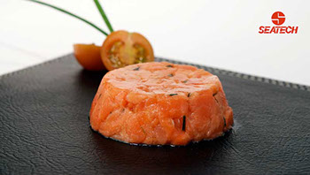 A photograph of salmon tartar with a sliced cherry tomato and chives in the background.