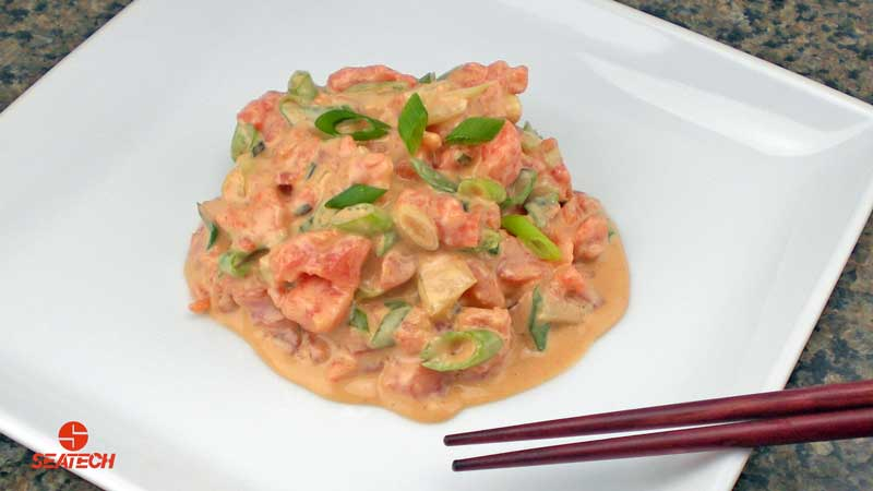 A photograph of spicy salmon tartar poke with salmon tartar, green onions and soy sauce mixed with mayonnaise and sriracha sauce.