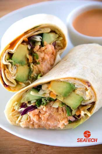 A photograph of a sriracha crunch salmon wrap with dipping sauce.